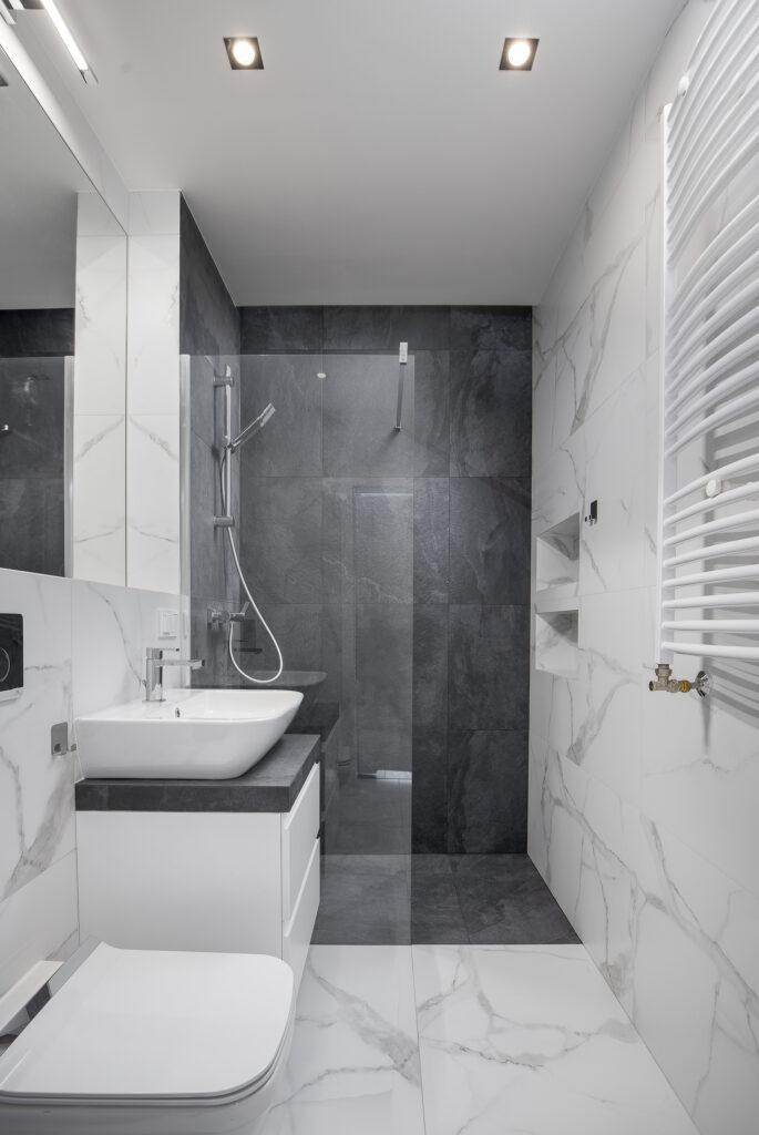 Łazienka zkabiną prysznicową walk-in, marmurowe iciemne płytki ceramiczne