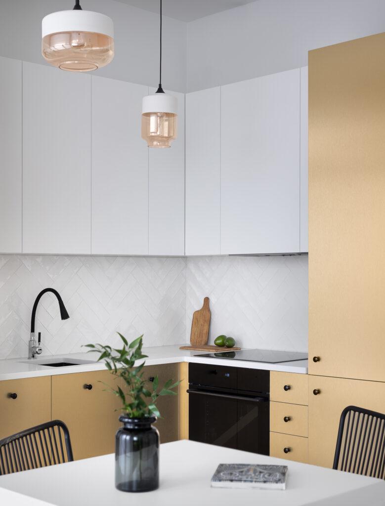 Aneks kuchenny zezłoto-białą zabudową kuchenną ipłytkami układanymi wjodełkę