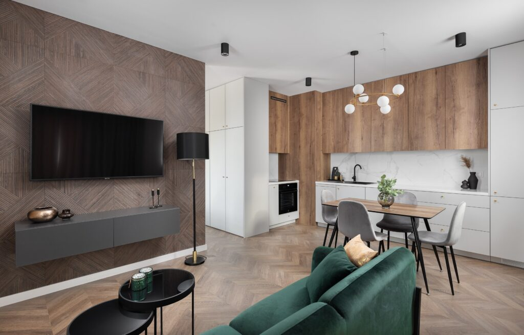 Salon zaneksem kuchennym, ozdobna ściana dekoracyjna, zielona kanapa, funkcjonalna zabudowa kuchenna