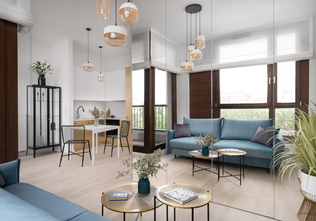 Mieszkanie typu studio zdużą lustrzaną szafą, niebieską kanapą izłotą zabudową kuchenną