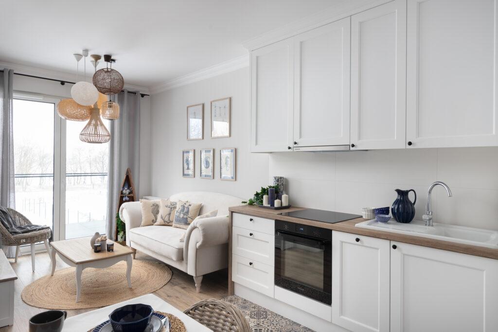 salon z białym aneksem kuchennym